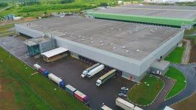Εναέριο κτήριο αποθήκευσης άποψης με τα φορτηγά στην κεκλιμένη ράμπα την ημέρα φιλμ μικρού μήκους