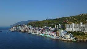 Εναέριο μήκος σε πόδηα πανοράματος κηφήνων της ζωηρόχρωμης εικονικής παράστασης πόλης στα βουνά πέρα από τη θάλασσα, Ευρώπη, πυκν φιλμ μικρού μήκους