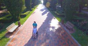 Εναέριο μήκος σε πόδηα του caregiver που περπατά με το με ειδικές ανάγκες πρεσβύτερο στην αναπηρική καρέκλα απόθεμα βίντεο