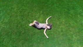 Εναέριο να βρεθεί γυναικών άποψης στην πράσινη χλόη απολαμβάνει τη ζωή, αισθάνεται το ευτυχές, ξένοιαστο καλοκαίρι απόθεμα βίντεο
