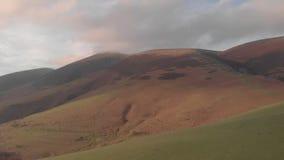 Εναέριο οπίσθιο μήκος σε πόδηα mountainside με μια misty σύνοδο κορυφής κάτω απ φιλμ μικρού μήκους