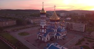 Εναέριο πέταγμα γύρω από τη νέα εκκλησία στη μικρή πόλη Χριστιανικός ναός και χρυσός θόλος εκκλησιών στην αυγή 4K απόθεμα βίντεο