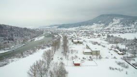 Εναέριο πέταγμα επάνω από τον ποταμό το χειμώνα ποταμός που γλιστρά μέσω της ζάλης του χιονώδους χειμερινού τοπίου απόθεμα βίντεο