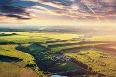 Εναέριο πανόραμα τοπίων φύσης άποψης μαγικό ζωηρό με τα μεγαλοπρεπείς δραματικούς σύννεφα και τους τομείς άνωθεν Στοκ Εικόνες
