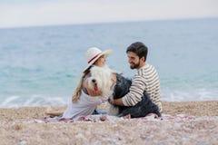 Εναλλακτική οικογένεια με μια κυρία ένα άτομο και ένα σκυλί μαζί στην παραλία που απολαμβάνει ένα πικ-νίκ στη φιλία και το parten στοκ εικόνες