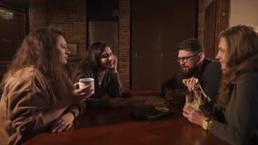 Ενδιαφέροντες φίλοι που κουβεντιάζουν ο ένας με τον άλλον πίνοντας τα ποτά σε έναν καφέ απόθεμα βίντεο