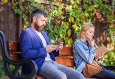 Ενδιαφέρουσα λογοτεχνία Έννοια χόμπι ανάγνωσης Η γυναίκα διάβασε το βιβλίο ενώ ο άνδρας διάβασε ebook το smartphone Διαβάστε το β στοκ φωτογραφία με δικαίωμα ελεύθερης χρήσης