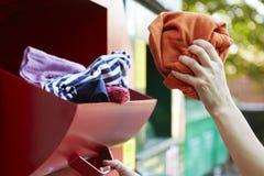 Ενδύματα ανακύκλωσης γυναικών στην τράπεζα ιματισμού Στοκ Φωτογραφίες