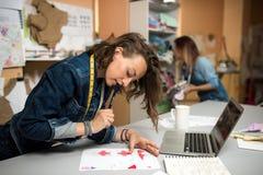 Ενδύματα και μοδίστρα σχεδιαστών, που λειτουργούν στο εργαστήριο Στοκ Εικόνες