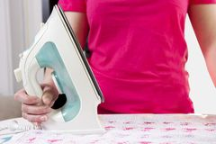 Ενδύματα σιδερώματος γυναικών στο σπίτι κορίτσι που κρατά έναν σίδηρο στο σιδερώνοντας πίνακα Στοκ Εικόνα
