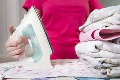 Ενδύματα σιδερώματος νοικοκυρών στο σιδέρωμα του πίνακα Σίδηρος στο χέρι γυναικών ` s οικιακά Σιδέρωμα των ενδυμάτων μετά από την Στοκ εικόνα με δικαίωμα ελεύθερης χρήσης