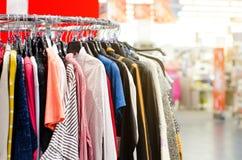 Ενδύματα στις κρεμάστρες στο κατάστημα στοκ εικόνα με δικαίωμα ελεύθερης χρήσης