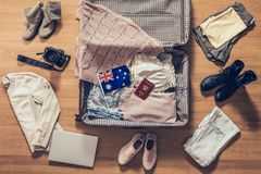 Ενδύματα, lap-top, κάμερα και σημαία γυναίκας της Αυστραλίας που βρίσκεται στο πάτωμα παρκέ κοντά και στην ανοικτή βαλίτσα r στοκ φωτογραφίες