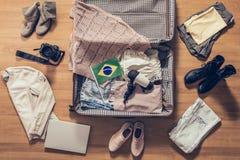 Ενδύματα, lap-top, κάμερα και σημαία γυναίκας της Βραζιλίας που βρίσκεται στο πάτωμα παρκέ κοντά και στην ανοικτή βαλίτσα r στοκ εικόνες με δικαίωμα ελεύθερης χρήσης