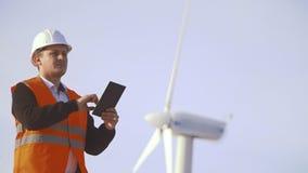 Ενεργειακός μηχανικός του ανεμόμυλου για να εργαστεί με την ταμπλέτα στο ηλιοβασίλεμα περιβαλλοντικός φιλμ μικρού μήκους