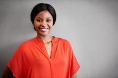 Ενεργητικό χαμόγελο στη κάμερα από την ελκυστική μαύρη γυναίκα ενάντια στο γκρι Στοκ Εικόνες
