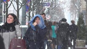 Ενεργοί νέοι που περπατούν το φθινόπωρο χιονοθυελλών ισχυρής χιονόπτωσης στο χειμώνα απόθεμα βίντεο