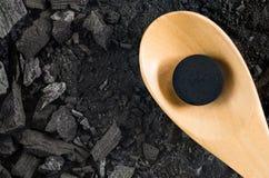 Ενεργοποιημένη ιατρική χαπιών άνθρακα στο ξύλινο κουτάλι στον επίγειο ξυλάνθρακα Στοκ Εικόνες