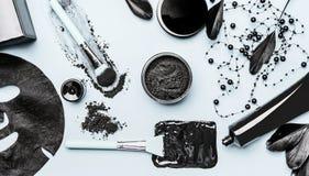 Ενεργοποιημένο του προσώπου καλλυντικό ξυλάνθρακα που θέτει με τη σκόνη, τη μαύρη επικεφαλής μάσκα, τη μάσκα φύλλων και τα εξαρτή στοκ εικόνες