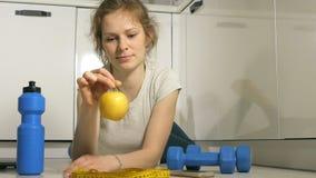 Ενεργός αθλητική αθλητική γυναίκα με την πετσέτα στην αθλητική εξάρτηση που τρώει το μήλο μετά από την κατάρτιση φιλμ μικρού μήκους