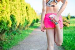 Ενεργός γυναίκα που κάνει τη ρουτίνα προθέρμανσης στο πάρκο πρίν τρέχει, τεντώνοντας τους μυς ποδιών με το μόνιμο ενιαίο γόνατο σ στοκ εικόνες