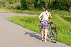 Ενεργός ζωή Μια γυναίκα με ένα ποδήλατο απολαμβάνει τη θέα στο θερινό δασικό ποδήλατο και την έννοια οικολογίας στοκ φωτογραφία