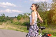 Ενεργός ζωή Μια γυναίκα με ένα ποδήλατο απολαμβάνει τη θέα στο θερινό δάσος στοκ φωτογραφία με δικαίωμα ελεύθερης χρήσης