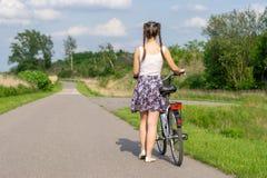 Ενεργός ζωή Μια νέα γυναίκα με την ανακύκλωση στο ηλιοβασίλεμα στο πάρκο Ποδήλατο και έννοια οικολογίας στοκ φωτογραφία με δικαίωμα ελεύθερης χρήσης