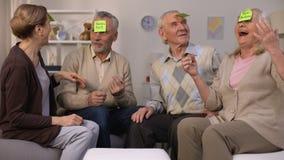 Ενεργός ηλικιωμένος άνθρωπος που παίζει ποιες είναι συνεδρίαση παιχνιδιών ι στο άνετο καθιστικό, ελεύθερος χρόνος απόθεμα βίντεο