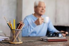 Ενεργός ηλικιωμένη συνεδρίαση ατόμων στο επιτραπέζιο στο σπίτι γραφείο Στοκ Εικόνες