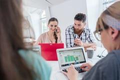 Ενεργός θηλυκός επιχειρηματίας που μιλά σε κινητό σε ένα κοινό γραφείο μέσα Στοκ Εικόνες