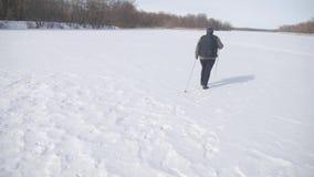 Ενεργός μια ηλικιωμένη γυναίκα συμμετείχε στο σκανδιναβικό περπάτημα με τα ραβδιά στην έννοια χειμερινού δασική υγιή τρόπου ζωής  απόθεμα βίντεο