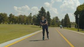 Ενεργός νέα γυναίκα που οδηγά στις λεπίδες κυλίνδρων στο πάρκο απόθεμα βίντεο