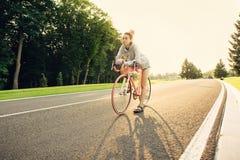 Ενεργός νέα γυναίκα στο ποδήλατο στο ηλιοβασίλεμα Στοκ φωτογραφία με δικαίωμα ελεύθερης χρήσης