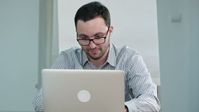 Ενεργός νέος δάσκαλος που σκέφτεται και που δακτυλογραφεί στο lap-top απόθεμα βίντεο
