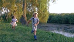 Ενεργός παιδική ηλικία, εύθυμα παιδιά που τρέχει και που παίζει τη σύλληψη στο χωριό στο ηλιοβασίλεμα φιλμ μικρού μήκους