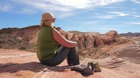 Ενεργός συνεδρίαση τουριστών γυναικών που στηρίζεται στις κόκκινες απόψεις βράχου και θαυμασμού του φαραγγιού απόθεμα βίντεο