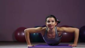 Ενεργός όμορφη γυναίκα που κάνει το γόνατο ώθηση-UPS εύκολα με το χαμόγελο στο πρόσωπο, γυμναστική workout απόθεμα βίντεο