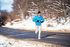 Ενεργό άτομο, που και που τρέχει κατά τη διάρκεια μιας ηλιόλουστης χειμερινής ημέρας Υπαίθρια επίλυση Στοκ Εικόνες