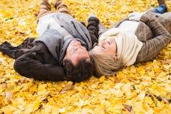 Ενεργό ανώτερο ζεύγος στο πάρκο φθινοπώρου που βρίσκεται στο έδαφος Στοκ φωτογραφίες με δικαίωμα ελεύθερης χρήσης