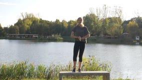 Ενεργό θηλυκό πρότυπο με την κατσαρωμένη τρίχα που κάνει τη γιόγκα μια ηλιόλουστη ημέρα του καλοκαιριού στη φύση κοντά στη λίμνη  απόθεμα βίντεο