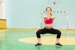 Ενεργό κορίτσι που εκτελεί τη στάση οκλαδόν σούμο στην αθλητική αίθουσα Στοκ φωτογραφίες με δικαίωμα ελεύθερης χρήσης