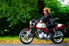 Ενεργό κορίτσι που οδηγά στη μοτοσικλέτα, σε αργή κίνηση Στοκ Φωτογραφία