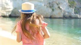 Ενεργό μικρό κορίτσι στην παραλία που έχει πολλή διασκέδαση φιλμ μικρού μήκους