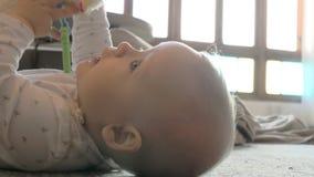 Ενεργό παιχνίδι κοριτσάκι με το παιχνίδι στο πάτωμα απόθεμα βίντεο