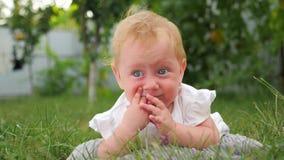 Ενεργό υπόβαθρο μωρών Προβλήματα οδοντοφυΐας μικρών παιδιών Κοριτσάκι που βρίσκεται στην πράσινη χλόη Μπροστινό υπόβαθρο κήπων απόθεμα βίντεο
