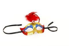 Ενετική μάσκα με το κόκκινες φτερό και την κορδέλλα Στοκ Φωτογραφίες