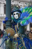 Ενετικός χαρακτήρας καρναβαλιού σε ένα ζωηρόχρωμες γαλαζοπράσινες και κίτρινες κοστούμι και μια μάσκα Βενετία καρναβαλιού peacock στοκ φωτογραφίες με δικαίωμα ελεύθερης χρήσης