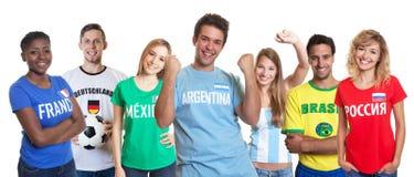Ενθαρρυντικός αργεντινός ανεμιστήρας ποδοσφαίρου με τη σφαίρα και την ενθαρρυντική ομάδα στοκ εικόνες