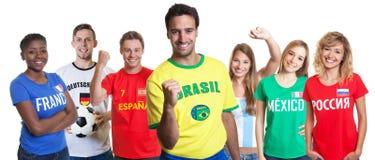 Ενθαρρυντικός βραζιλιάνος υποστηρικτής ποδοσφαίρου με τους ανεμιστήρες από άλλο countri στοκ φωτογραφίες